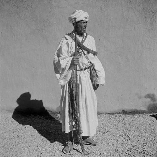 Agdz/ Guerrier en tenue traditionnelle de la haute vallée avec son fusil, moukala, ses sacs à poudre, son poignard, sa choukara, sa ceinture à balles passée en bandoulière.
