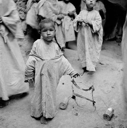 Boumalen du Dades: Enfant et son jouet fait de fil de fer et de boîtes de conserve.