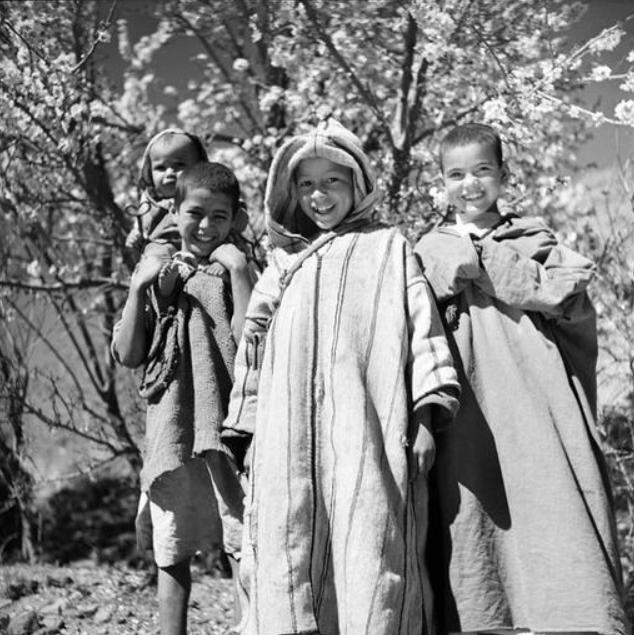 Haut Atlas: Jeunes Berbères de la région au sud de Marrakech, portant la djellaba. Le garçon au centre porte une djellaba de laine rayée et tissée sur le métier familial.