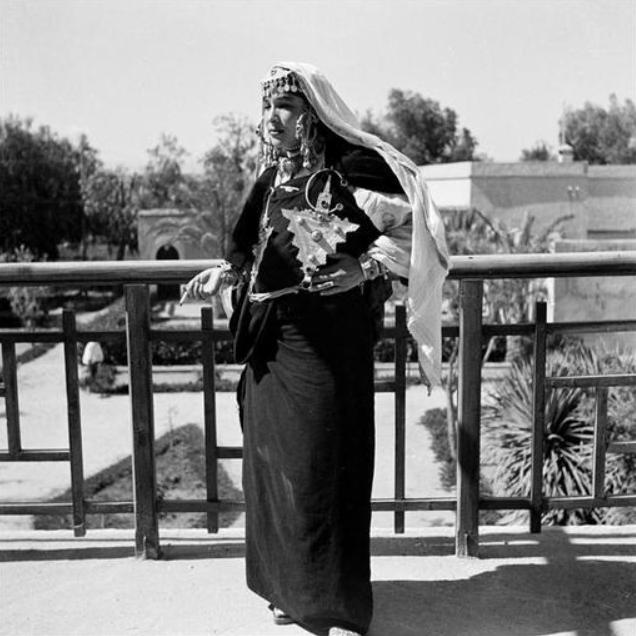 Tiznit/ Danseuse chleuh, chtakhat, vêtue d' un drapé de cotonnade noire, tamelhaft, tombant jusqu'au sol fixé devant par deux énormes fibules, tizerzaï, reliées entre elles par une