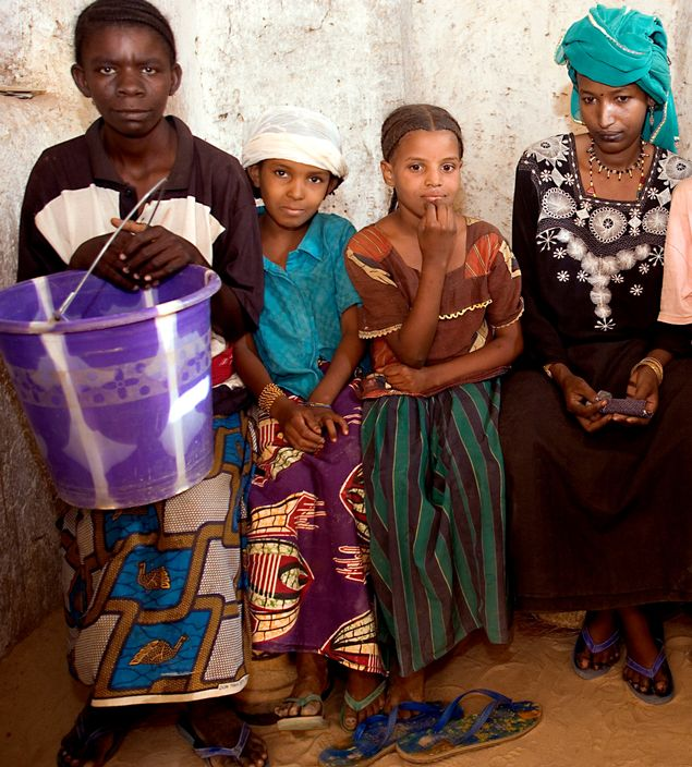 NIGER. Tajae. Khadijatou, Tuareg wife of the ex-chief of Tajae in the Tuareg palace with royal daughters Aminatou and Fatima and slave holding a bucket. 2005.
