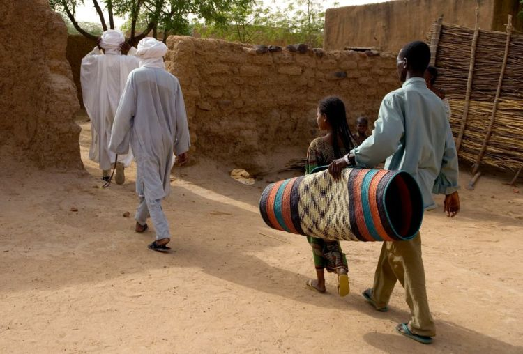 NIGER. Tajae. Tuareg slave Youssouff carries mat for Tuareg chieftan Ibrahim Agali (l) as he leaves palace with his cousin Sayadi Ibrahim (r). 2005.