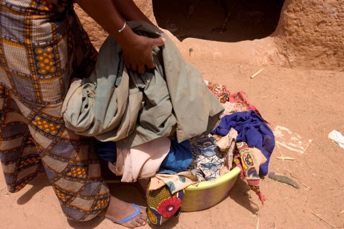 NIGER. Zangitchiga. Aishatou Agali, a slave, of 15 years old sorts through the washing she has to do for her Tuareg master. 2005.